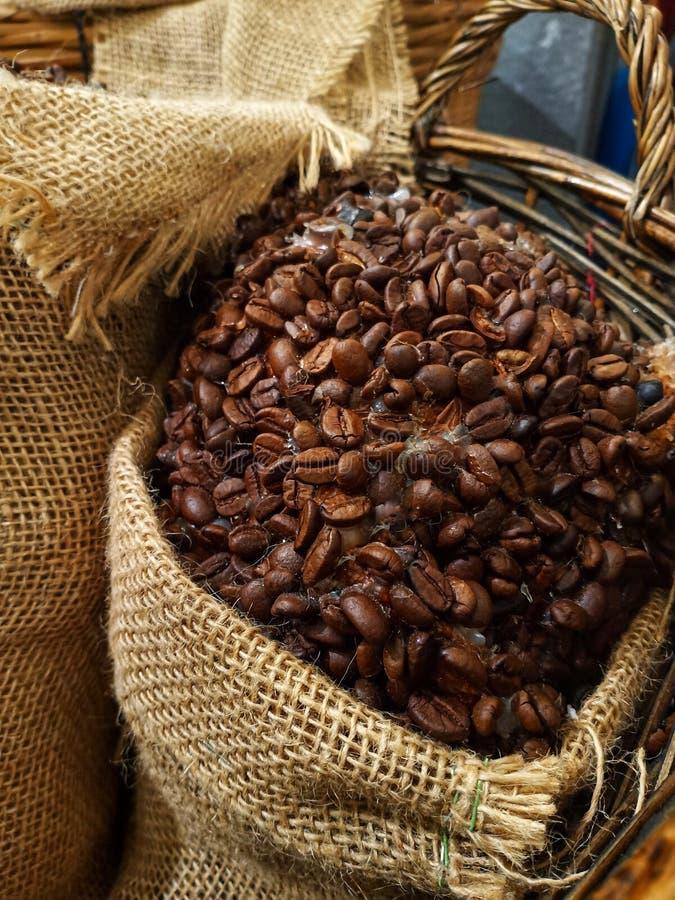 image haute étroite des grains de café dans un regard de cru de vêtements de sac image libre de droits
