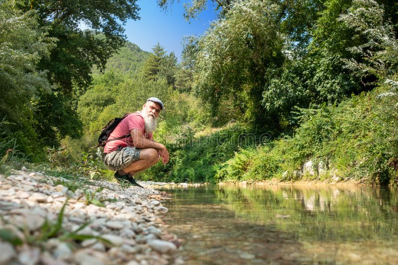 Hiker is resting by the stream stock photography