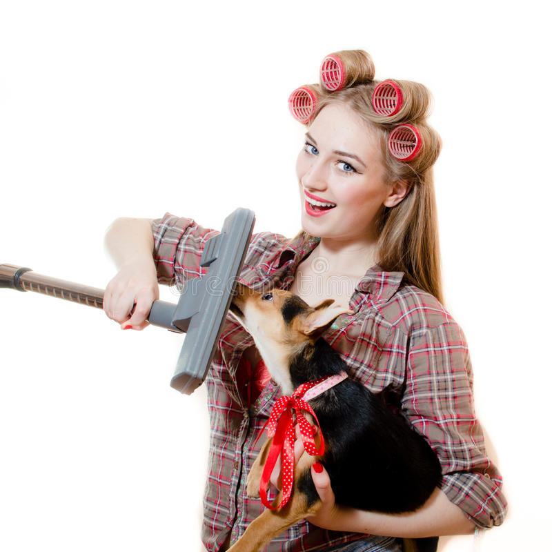 Image of holding cute puppy and vacuum cleaner beautiful pinup charming girl with blue eyes, curlers and red lips royalty free stock images