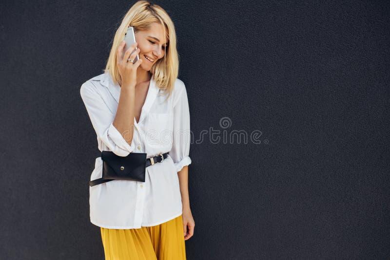 Image horizontale de la femme blonde d'affaires souriant et se tenant contre le mur du bâtiment gris tout en parlant au téléphone photographie stock libre de droits
