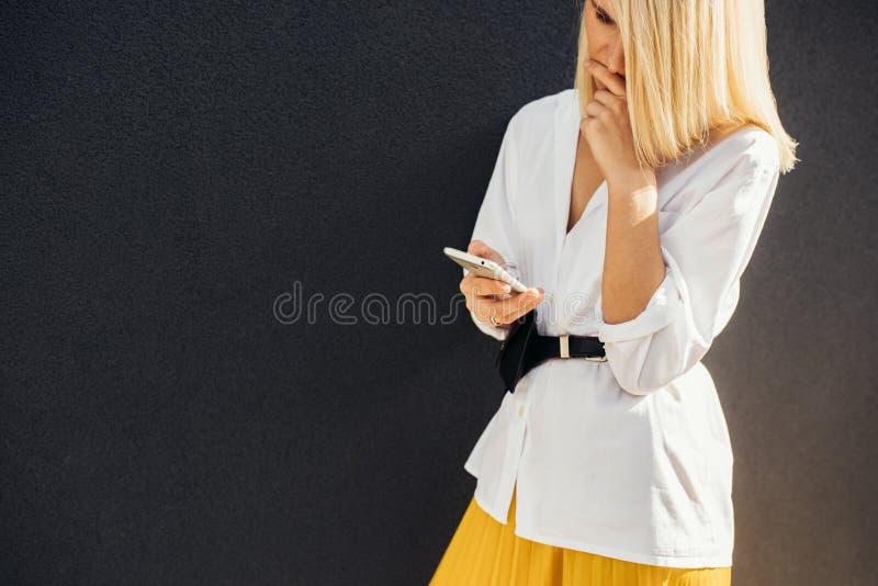Image horizontale de la lecture femelle blonde sérieuse, message textuel textotant au téléphone portable posant sur le mur gris e photographie stock