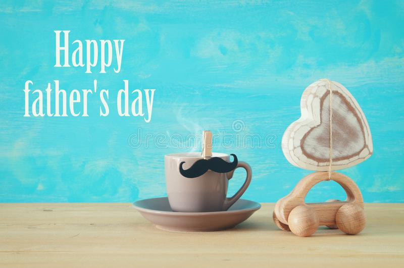 Image of hot coffee or tea next to toy car with heart over wooden table. Father`s day concept. Image of hot coffee or tea next to toy car with heart over wooden stock photos