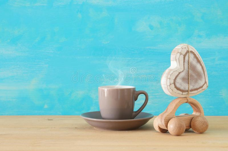 Image of hot coffee or tea next to toy car with heart over wooden table. Father`s day concept. Image of hot coffee or tea next to toy car with heart over wooden royalty free stock photo