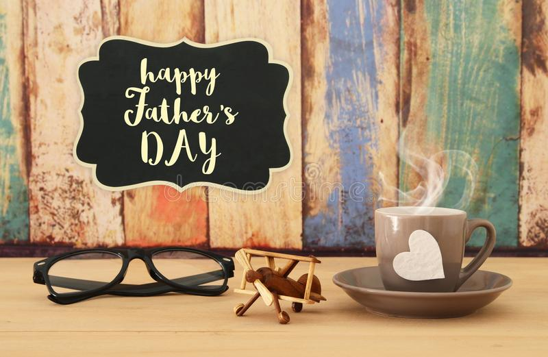 Image of hot coffee or tea, old plane toy and glasses over wooden table. Father`s day concept. Image of hot coffee or tea, old plane toy and glasses over wooden royalty free stock photos