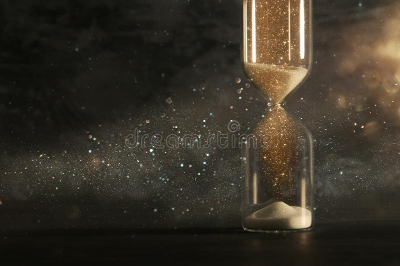 Image of hourglass as time passing concept over black background for business deadline. Glitter overlay. Image of hourglass as time passing concept over black royalty free stock photos