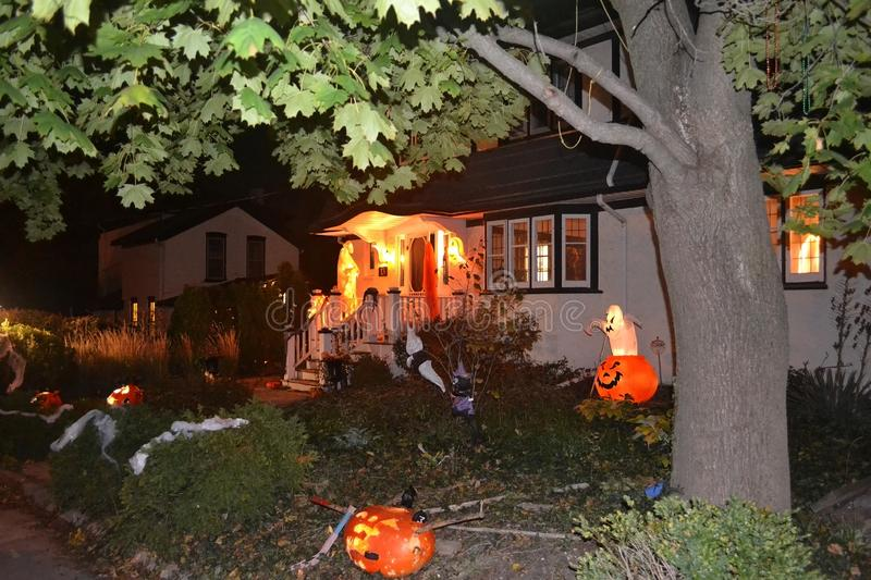 Image of a house in the night with Halloween decoration. A night picture of a nice decorated house with Halloween decoration.under a big tree stock image