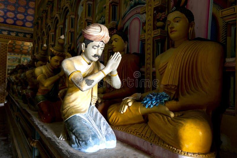 The Image House at Wewurukannala Vihara at Dickwella in Sri Lanka. A ray of sunshine lights a statue worshipping Buddha in the Image House at Wewurukannala stock photos