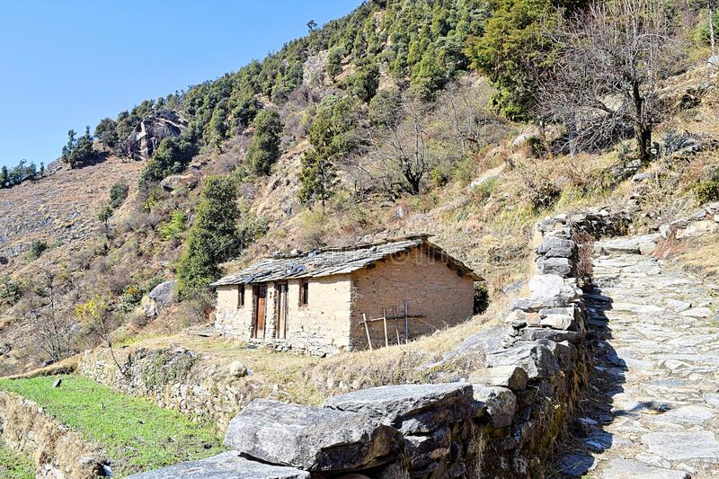 Hut in a Himalayan Village with Rocky Trek with Trees and Mountain in Background - Uttarakhand, India stock images