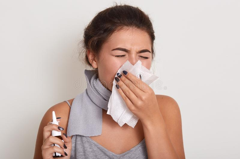 Image of ill allergic woman blowing running nose, having got flu or catch cold, sneezing in handkerchief, posing with closed eyes stock images