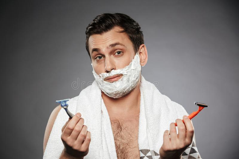 Image of indecisive man with shaving foam on his face holding two razors, isolated over gray background stock photo