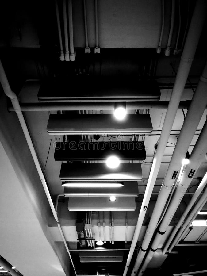 Monochrome indoor ceiling showing pipeline, lights, and electric lines royalty free stock photo