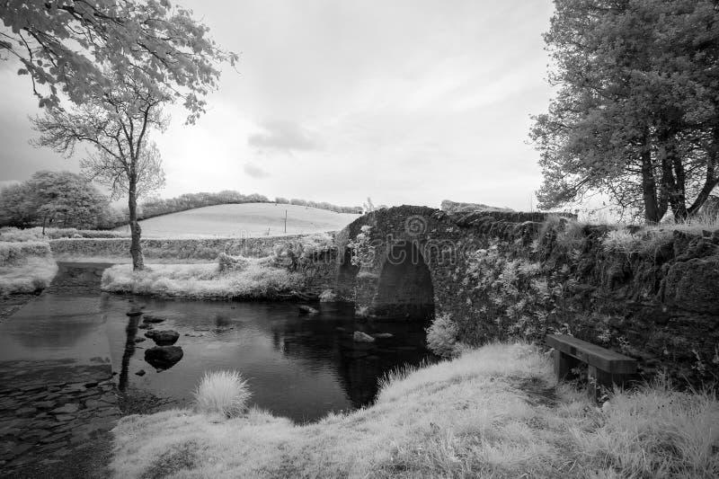 Image infrarouge noire et blanche renversante de paysage de vieux pont image stock