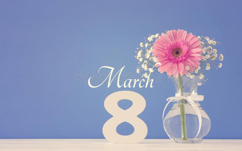 Image of International women day concept with beautiful flower in the vase on wooden table. royalty free stock photos