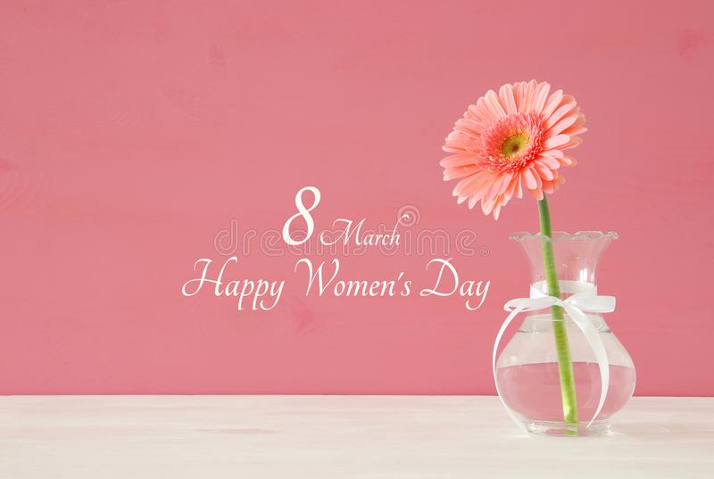 Image of International women day concept with beautiful flower in the vase on wooden table. royalty free stock image