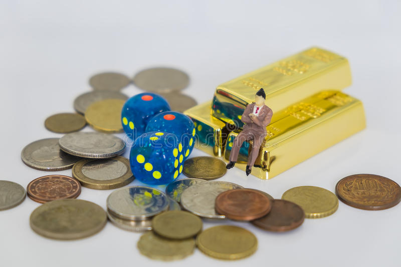Image of investment risk and return concept. Image of investment concept. The doll business man sitting on the gold bars with stacked coins and dices stock images