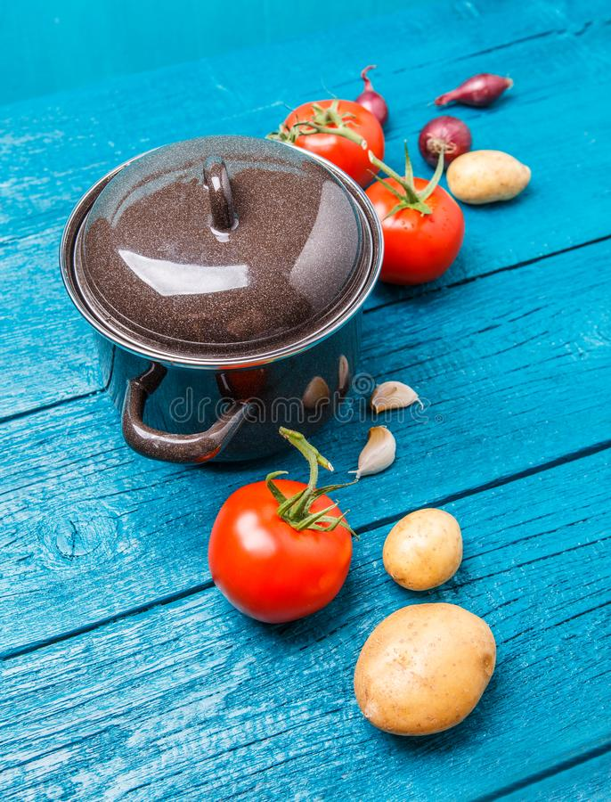 Image of iron pot for soup, tomato, potatoes, onions. On blue wooden background stock images