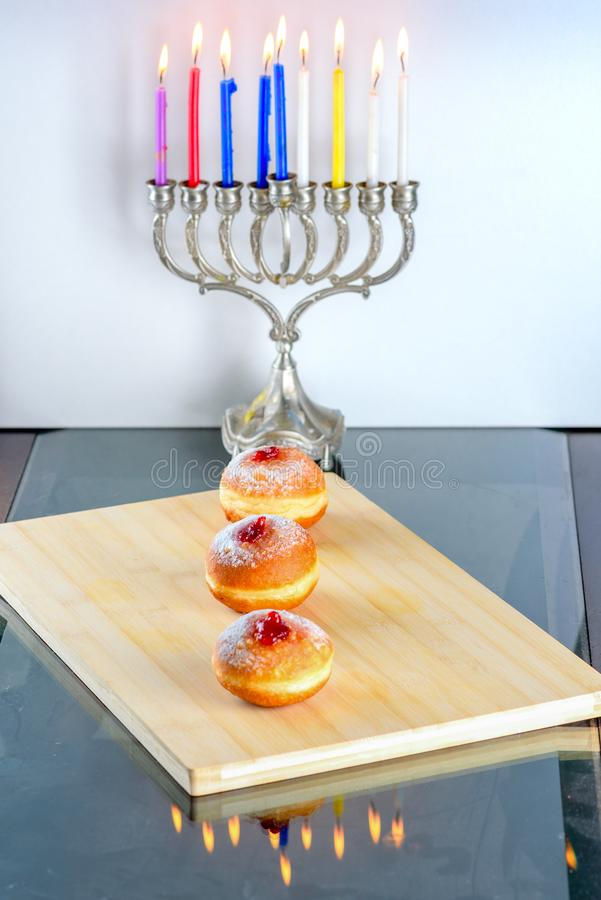Hanukkah celebration concept. Close up view of tasty donuts with jam and menorah traditional candelabra. royalty free stock photos