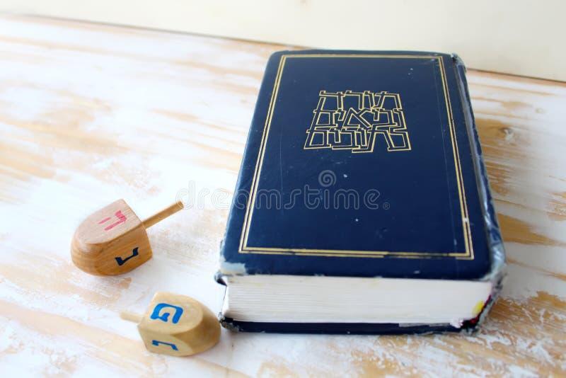 Image of Jewish holiday Hanukkah. Hebrew Bible Tanakh Torah, Neviim, Ketuvim and Wooden dreidels toys Hanukkah, holiday symbols royalty free stock photography