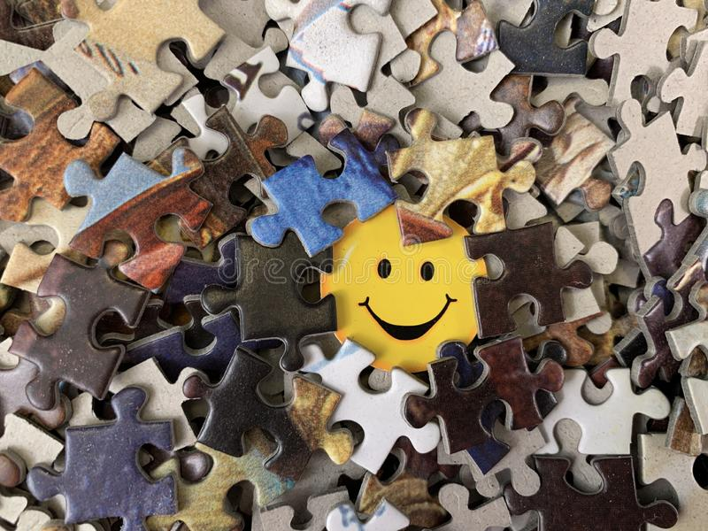 The image of a joyful face on cardboard. Puzzle in detail in a mosaic set. Concept: joy, happiness, positive, kindness stock photos