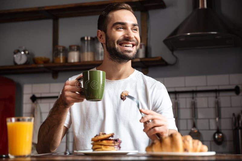 Image of joyful guy 30s eating food while having breakfast in modern apartment. Image of joyful guy 30s sitting at table and eating food while having breakfast stock photography
