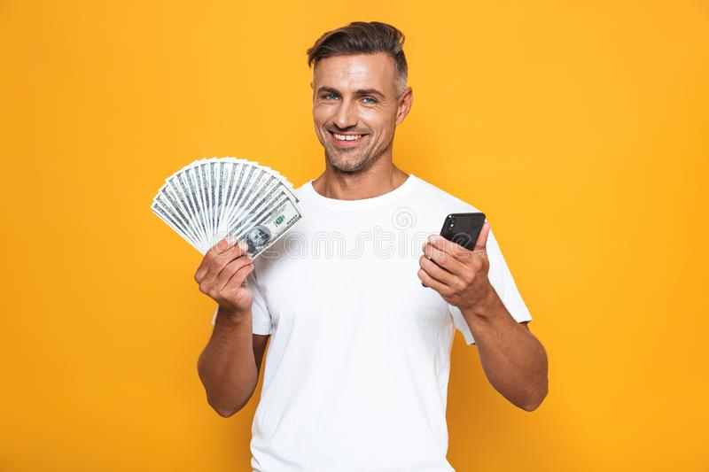Image of joyful guy 30s in white t-shirt holding cell phone and bunch of money. Isolated over yellow background stock photography