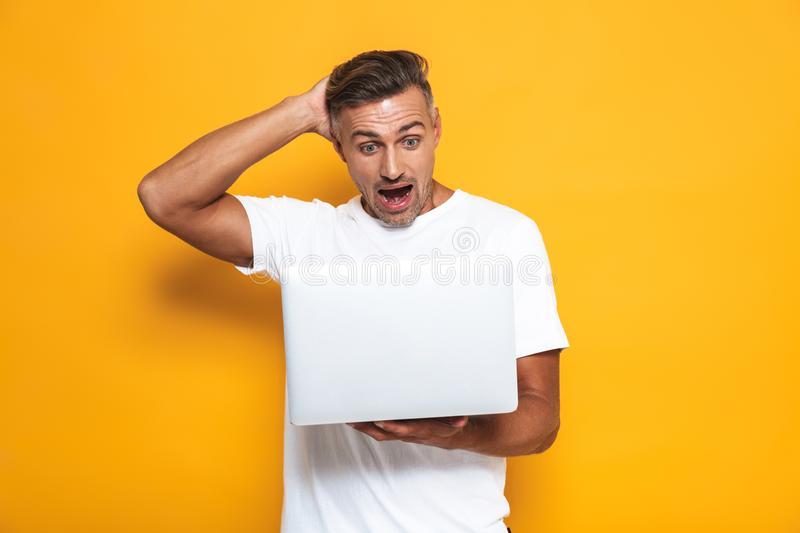 Image of joyful guy 30s in white t-shirt holding and using silver laptop. Isolated over yellow background stock photos