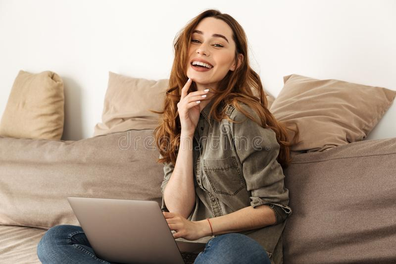 Image of joyful woman 20s with brown hair sitting on sofa in living room with legs crossed, and using laptop looking on camera stock photography