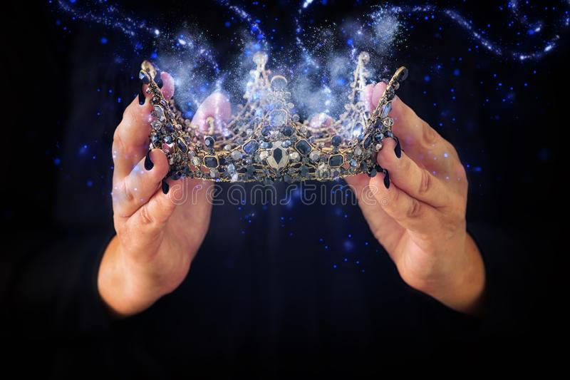 image of lady in black holding queen crown decorated with precious stones and magical glowing mysterious dust. fantasy medieval p royalty free stock photo