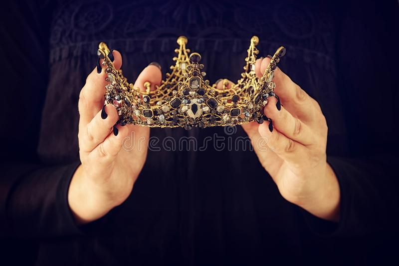 Image of lady in black with holding queen crown decorated with p. Recious stones. fantasy medieval period. Black queen stock photo
