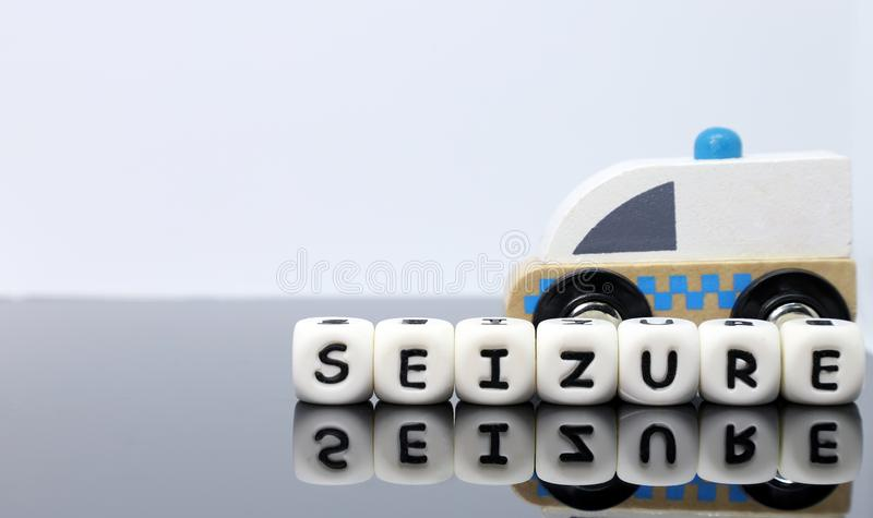 A model ambulance and a word seizure. Image of letters spelling a word seizure and a model ambulance on a reflecting background stock photos