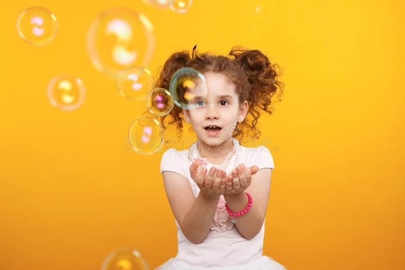 Close up of a little curly girl in studio over yellow backgrounds. Frontal portrait of little girl catch flying bubbles. stock image