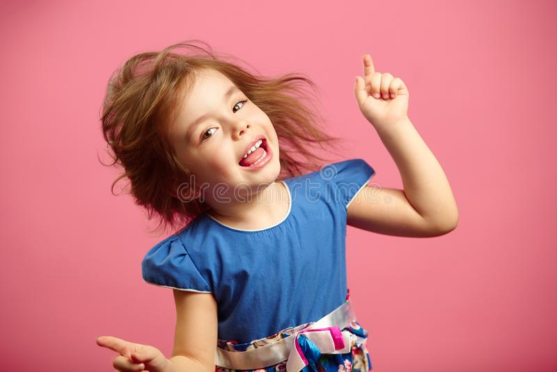 Image of little dancing girl wears beautiful dress on isolated pink background. royalty free stock photos
