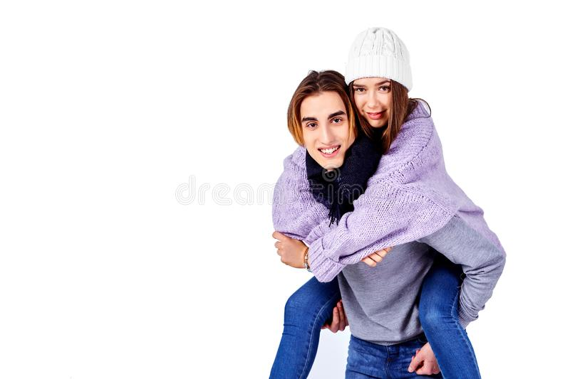 Image of lovely couple having fun while man piggybacking his girlfriend isolated on white background royalty free stock photography