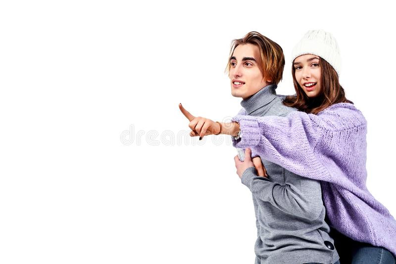Image of lovely couple having fun while man piggybacking his girlfriend isolated on white background royalty free stock image