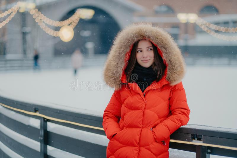 Image of lovely thoughtful young woman wears winter red coat with fur on hoody, keeps hands in pockets, stands against blurred stock photo
