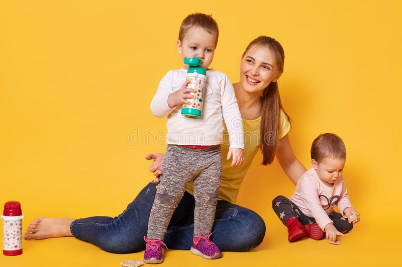 Image of loving attractive mother looks after her little children, twins playing with mommy. Playful kids drink tasty baverage stock photography