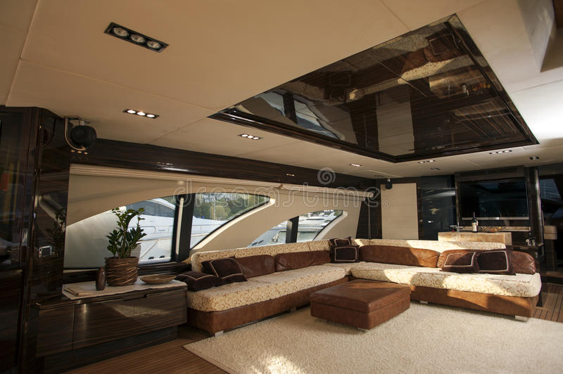 Image of luxury ship interior, comfortable sailboat cabin, expensive wooden design and soft white sofa inside on the yacht royalty free stock image