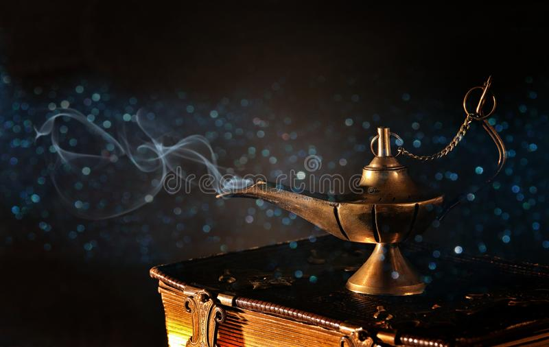 Image of magical aladdin lamp on old books. Lamp of wishes. stock images