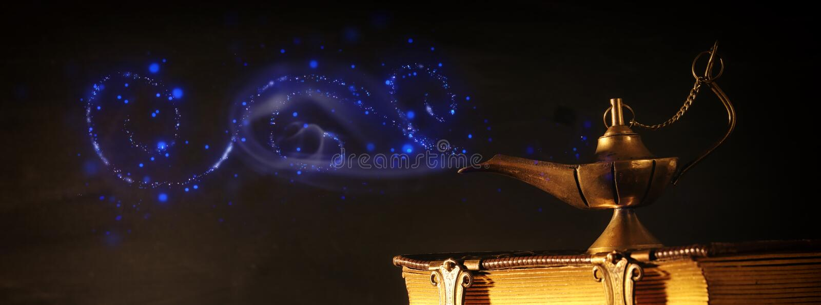 Image of magical aladdin lamp and old books. Lamp of wishes stock image