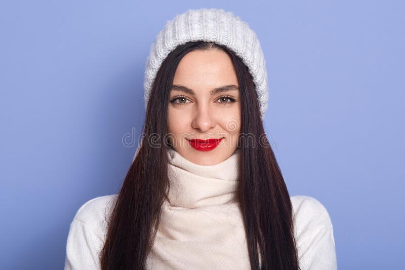 Image of magnetic attractive young black haired woman looking directly at camera, having red lips, wearing hat, sweater and scarf stock photos