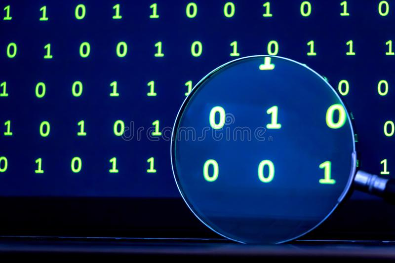 Magnifying Glass Searching for Code from Binary Data. Image of a magnifying glass on keyboard of a laptop computer magnifying binary data on its screen by night stock photos