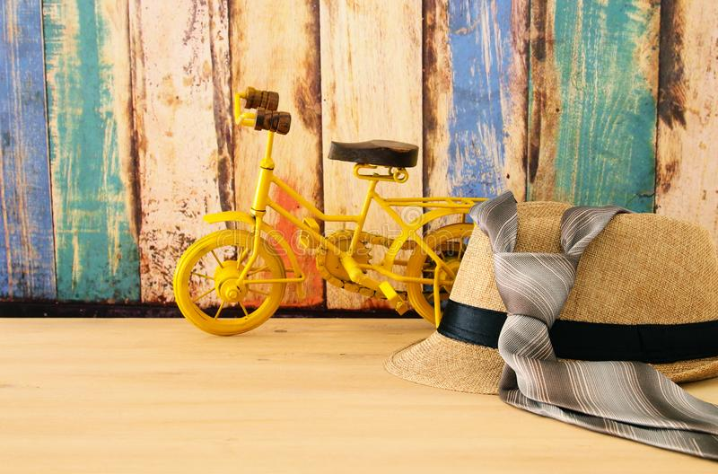 Image of male fedora hat and bicycle toy over wooden table. Father`s day concept. Image of male fedora hat and bicycle toy over wooden table. Father`s day royalty free stock photo