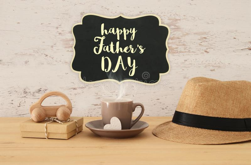 Image of male fedora hat, cup of hot coffee or tea and car toy o. Ver wooden table. Father`s day concept royalty free stock photo