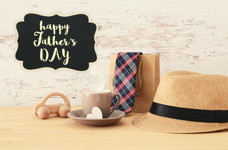 Image of male fedora hat, cup of hot coffee or tea and car toy o. Ver wooden table. Father`s day concept stock photo