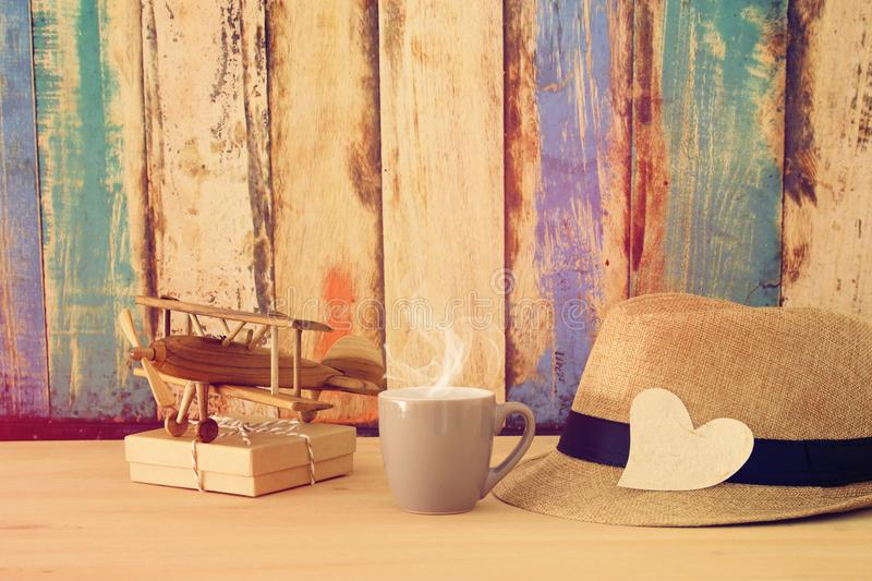 Image of male fedora hat, cup of hot coffee or tea and plane toy over wooden table. Father`s day concept. Image of male fedora hat, cup of hot coffee or tea and stock photos