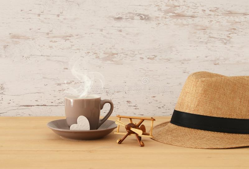 Image of male fedora hat, cup of hot coffee or tea and plane toy. Over wooden table. Father`s day concept royalty free stock photo