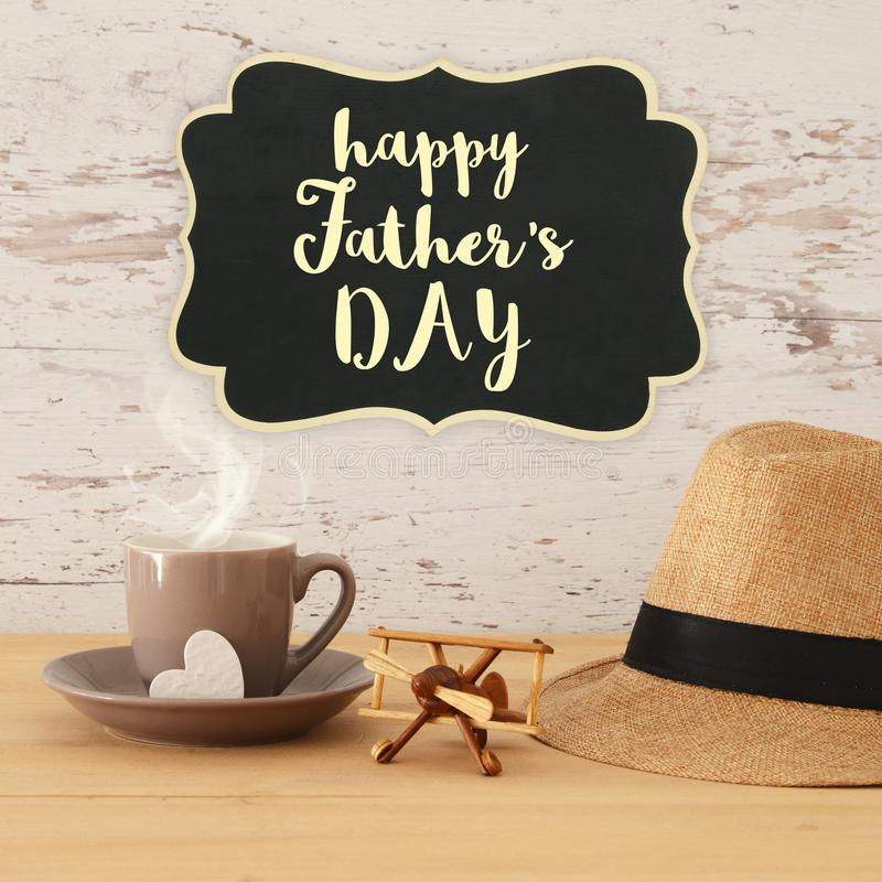 Image of male fedora hat, cup of hot coffee or tea and plane toy over wooden table. Father`s day concept. Image of male fedora hat, cup of hot coffee or tea and stock image