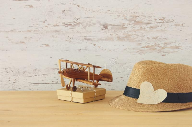 Image of male fedora hat and plane toy over wooden table. Father. `s day concept stock photos