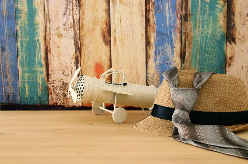 Image of male fedora hat and plane toy over wooden table. Father`s day concept. Image of male fedora hat and plane toy over wooden table. Father`s day concept stock photo