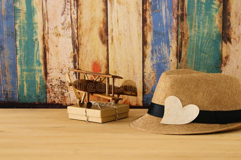 Image of male fedora hat and plane toy over wooden table. Father`s day concept. Image of male fedora hat and plane toy over wooden table. Father`s day concept stock photography